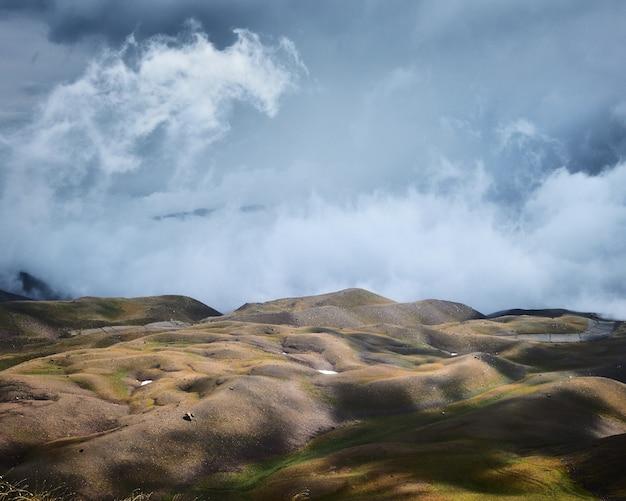Mooi schot van lege met gras begroeide heuvels onder een blauwe bewolkte hemel Gratis Foto