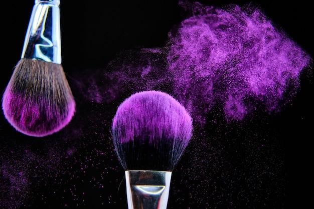 Mooi schot van make-upborstel die op zwarte achtergrond wordt geïsoleerd Gratis Foto