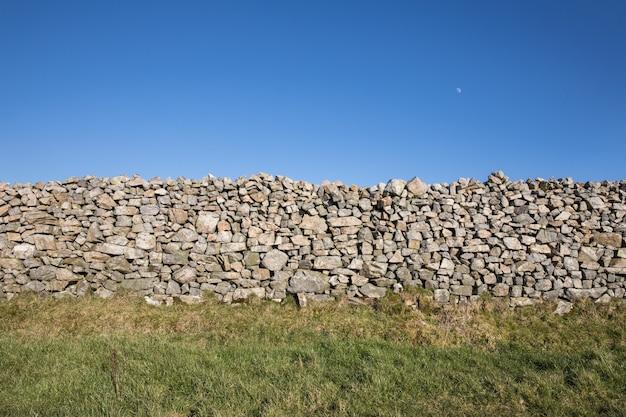 Mooi schot van stenen muur in een groen veld onder een heldere hemel Gratis Foto