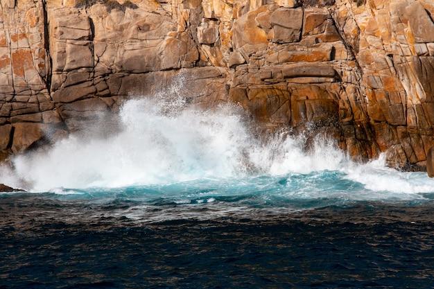 Mooi schot van sterke zeegolven die op de klif slaan Gratis Foto