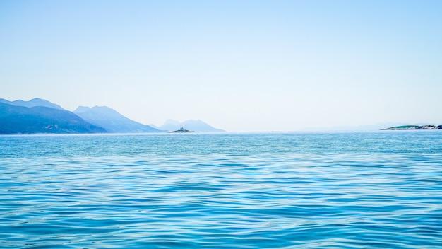 Mooi schot van zee met een berg in de verte en een heldere hemel Gratis Foto