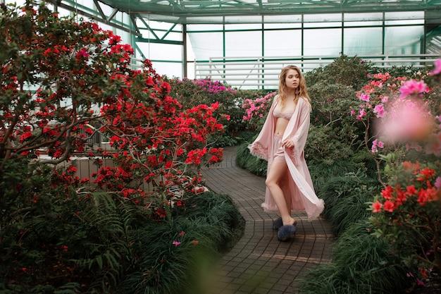 Mooi sexy meisje die roze badjas en lingerie dragen die zich in bloemtuin bevinden. Gratis Foto
