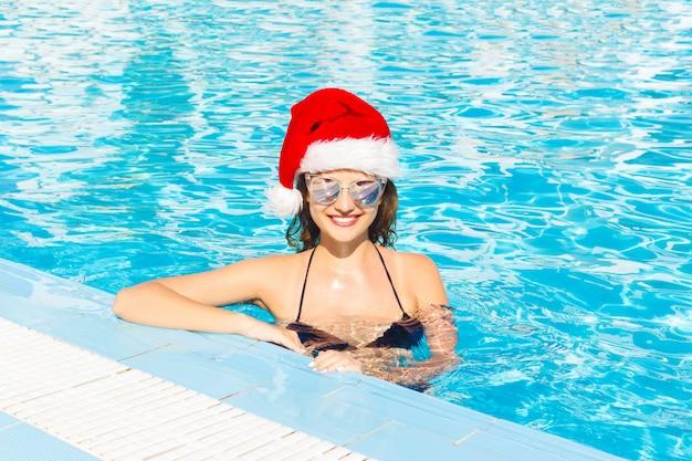 Mooi sexy meisje in kerstman hoed met gebruinde huid in zwarte bikini zonnebril. schoon water in het spahotel op vakantie Premium Foto