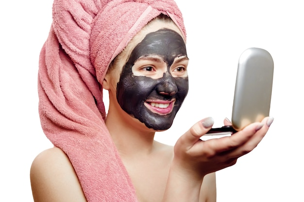 Mooi sexy meisje met zwart gezichtsmasker op de witte achtergrond, close-up portret, geïsoleerde, roze handdoek op haar hoofd, meisje kijkt met plezier naar zichzelf in een kleine spiegel, glimlacht Premium Foto