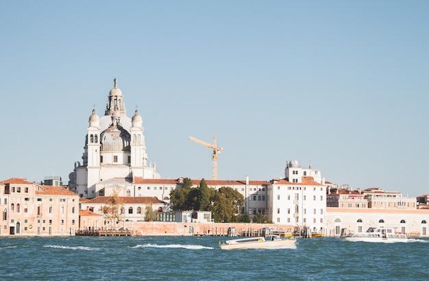 Mooi shot van een boot op het water en het bouwen in de verte in venetië canals Gratis Foto