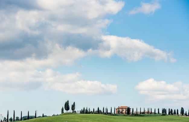 Mooi shot van een grasveld met bomen en een huis in de verte onder een blauwe hemel Gratis Foto