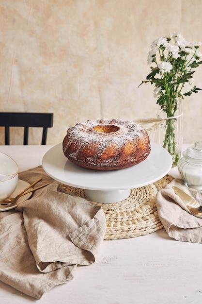 Mooi shot van een heerlijke ringcake op een witte plaat en een witte bloem erbij Gratis Foto