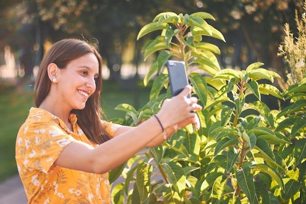 Mooi shot van een jong meisje in een geel overhemd dat een selfie naast struiken neemt Gratis Foto