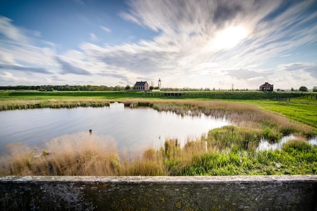 Mooi shot van een klein meer omgeven door groen onder een bewolkte hemel Gratis Foto