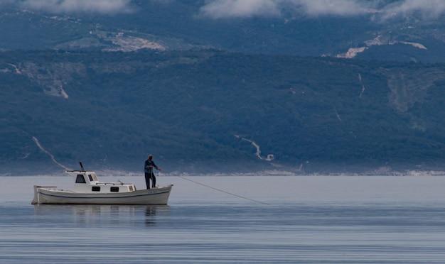 Mooi shot van een man op een boot die vis vangt in het meer met bergen op de achtergrond Gratis Foto