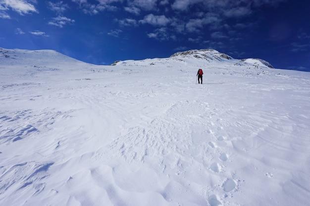 Mooi shot van een wandelaar die met een rode reisrugzak een berg oploopt onder de blauwe lucht Gratis Foto