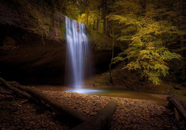 Mooi shot van een waterval, omringd door herfst bomen en bladeren in een bos Gratis Foto