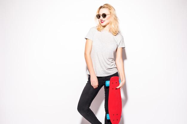 Mooi skater meisje in grijze t-short blijft voor witte muur Gratis Foto