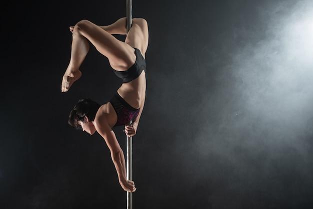 Mooi slank meisje met pyloon. vrouwelijke pooldanser die op een zwarte achtergrond danst Premium Foto