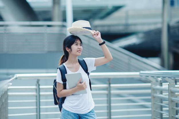 Mooi studentenmeisje die met laptop en zak, het concept van het onderwijs glimlachen Gratis Foto