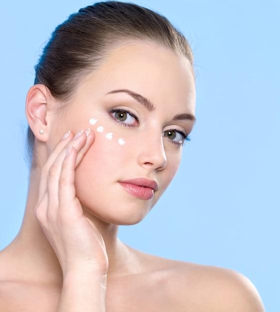 Mooi tienermeisje cosmetische crème toe te passen op de huid rond de ogen Gratis Foto