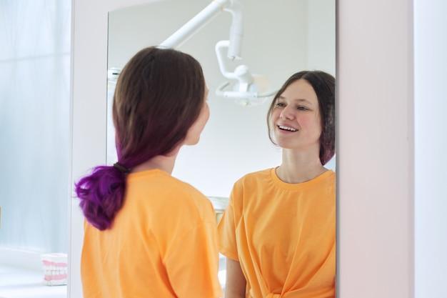 Mooi tienermeisje dat witte gezonde tanden in spiegel in tandartsbureau bekijkt Premium Foto