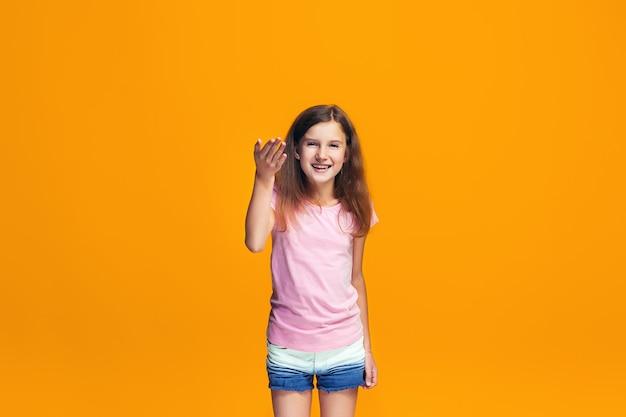 Mooi tienermeisje op zoek verrast geïsoleerd op oranje Gratis Foto