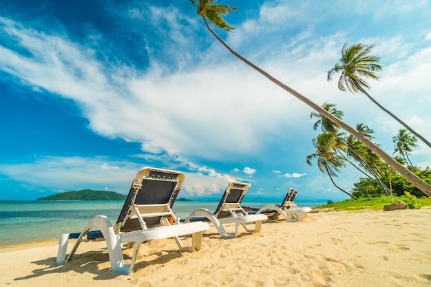 Mooi tropisch strand en zee met kokosnotenpalm en stoel in paradijseiland Gratis Foto
