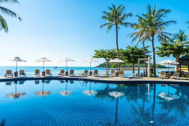 Mooi tropisch strand en zee met paraplu en stoel rond zwembad Gratis Foto