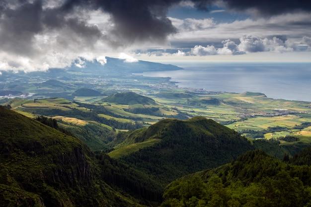 Mooi uitzicht groene vallei aan zee vanuit hoge bergen met wolken. sao miguel. azoren Premium Foto