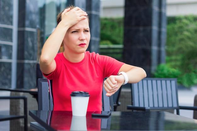 Mooi verdrietig boos nerveus meisje met hoofd met hand, herinnerde zich dat ze iets was vergeten of vergeten te doen. jonge vrouw haast, heeft geen tijd, kijkt op het horloge, controleert de tijd. cafe, koffie. Premium Foto