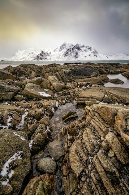 Mooi verticaal beeld van een rotsachtige atlantische kust met sneeuw bedekte berg Gratis Foto