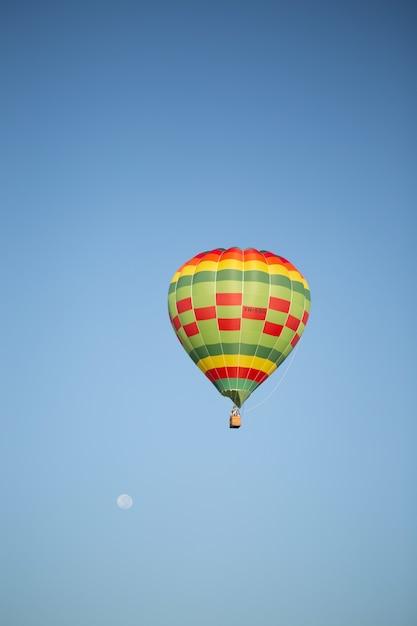 Mooi verticaal beeld van hete luchtballon over de schone blauwe hemel Gratis Foto