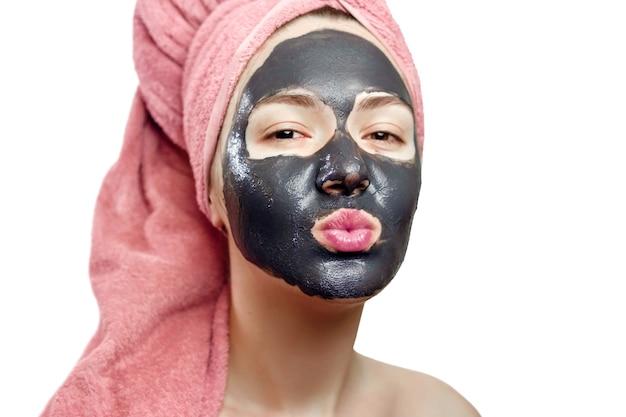 Mooi vrij sexy meisje met zwart gezichtsmasker op de witte achtergrond, close-up portret, geïsoleerd, meisje met een roze handdoek op haar hoofd, meisje stuurt een luchtkus, zwart masker op het gezicht van het meisje Premium Foto