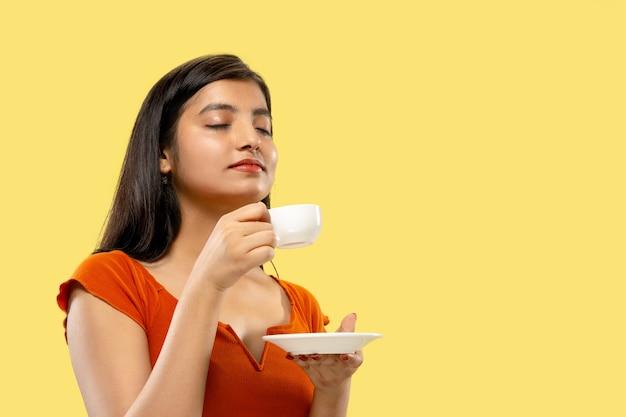 Mooi vrouwelijk geïsoleerd portret van halve lengte. jonge emotionele indiase vrouw in jurk koffie drinken. negatieve ruimte. gelaatsuitdrukking, concept van menselijke emoties. Gratis Foto