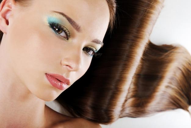 Mooi vrouwelijk gezicht met heldere ceremoniële make-up en weelderig gezondheidshaar Gratis Foto