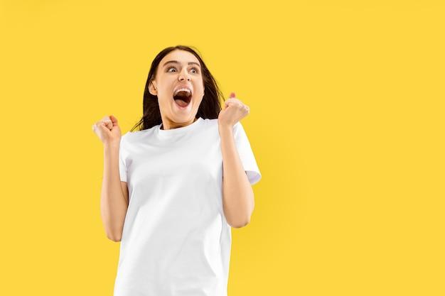 Mooi vrouwelijk portret van halve lengte dat op gele ruimte wordt geïsoleerd. jonge glimlachende vrouw. gelaatsuitdrukking, zomer, weekend, resortconcept Gratis Foto