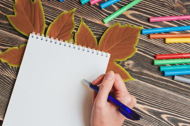 Mooi vrouwelijke hand schrijven in lege notitieblok op houten tafel Premium Foto
