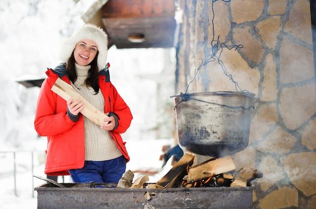 Mooi vrouwen kokend diner in de winter in openlucht. Premium Foto