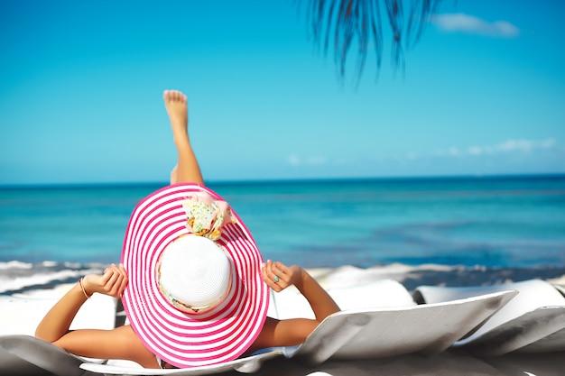 Mooi vrouwenmodel die op de strandstoel in witte bikini in kleurrijke sunhat achter de blauwe oceaan van het de zomerwater zonnebaden Gratis Foto