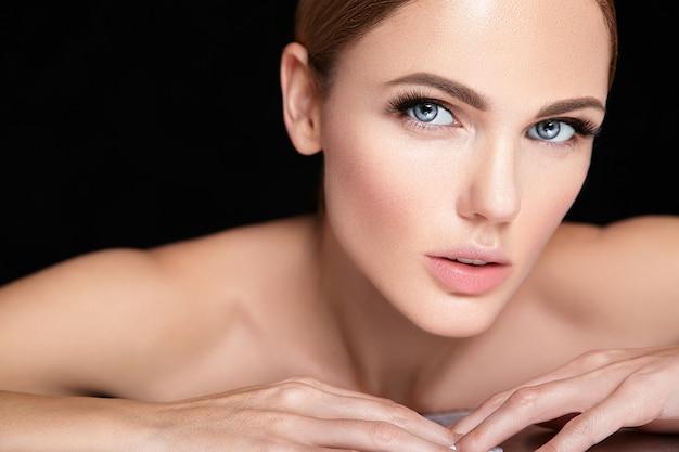 Mooi vrouwenmodel zonder make-up en schoon gezond huidgezicht op zwarte Gratis Foto