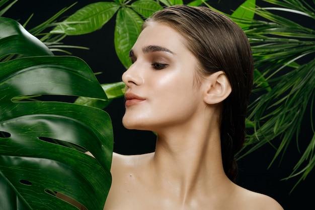 Mooi vrouwenportret in palmstruiken, mooie huid van het gezicht Premium Foto