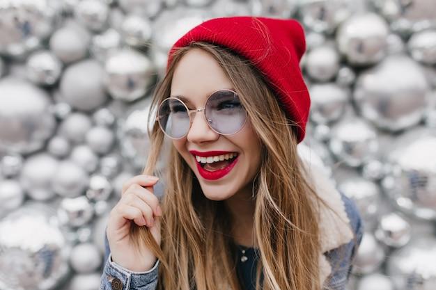 Mooi wit meisje dat en met haar blonde haar op glanzende muur lacht speelt. foto van schattig vrouwelijk model in trendy rode hoed gelukkige emoties uitdrukken. Gratis Foto