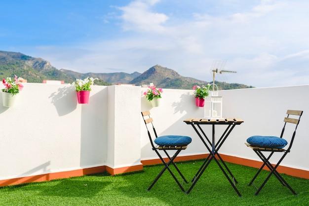 Mooi wit terras met stoelen en een koffietafel met uitzicht op de mediterrane mountai Premium Foto