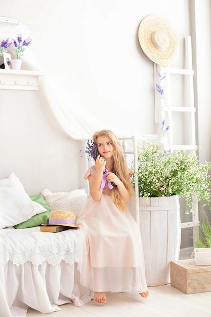 Mooi zit weinig glimlachend meisje op bed in slaapkamer met boeket van de zomerbloemen. meisje met een boeket van lavendel. Premium Foto