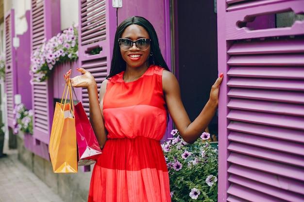 Mooi zwart meisje met boodschappentassen in een stad Gratis Foto
