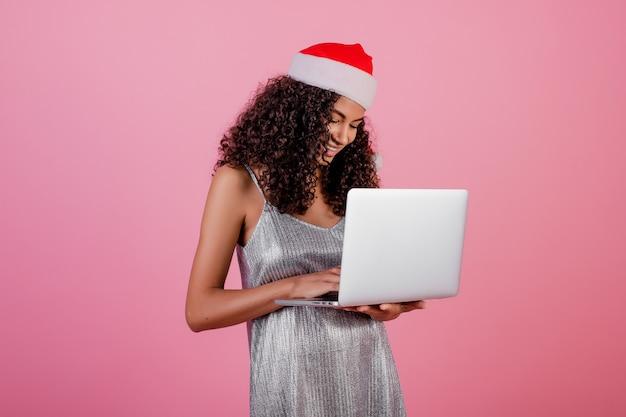 Mooi zwart meisje met laptop die de hoed en de kleding van vakantiekerstmis draagt die over roze wordt geïsoleerd Premium Foto