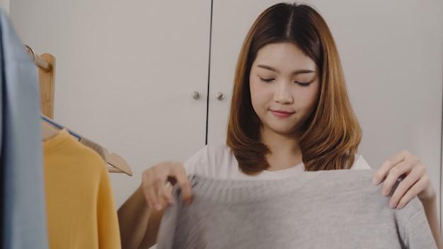Mooie aantrekkelijke jonge aziatische vrouw die haar kleren van de manieruitrusting thuis kiezen in kast Gratis Foto