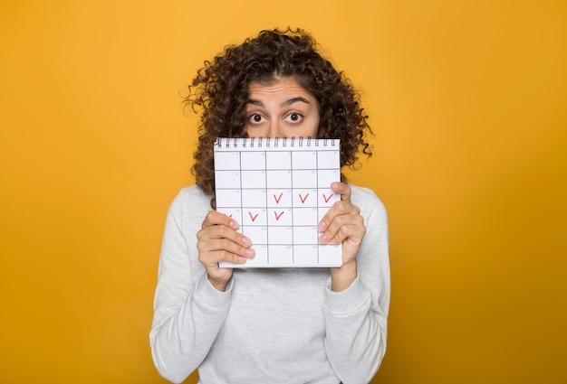 Mooie afrikaanse amerikaanse vrouw houdt markeert de dagen van de menstruatie in de kalenderperiode. Premium Foto