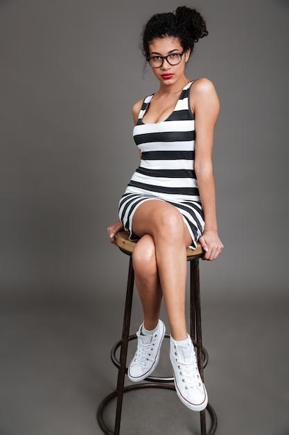 Mooie amerikaanse jonge vrouw zitten en poseren op stoel Gratis Foto