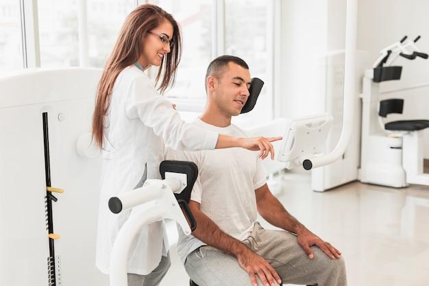 Mooie arts die patiënt toont hoe te om medisch hulpmiddel te gebruiken Gratis Foto