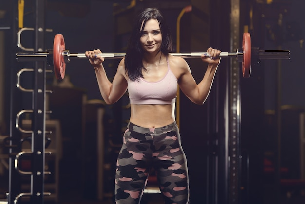 Mooie atletische jonge vrouw die in gymnastiek uitwerkt Premium Foto