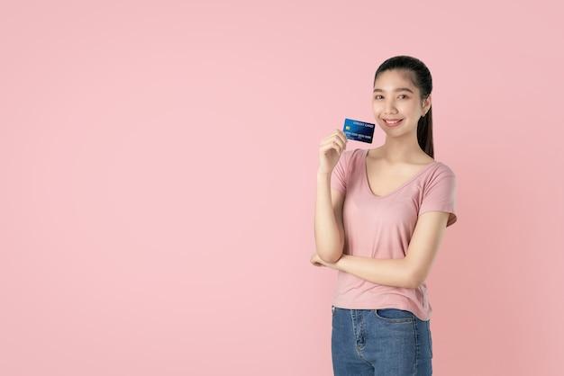 Mooie aziatische de creditcardbetaling van de vrouwenholding op roze achtergrond met exemplaarruimte. Premium Foto