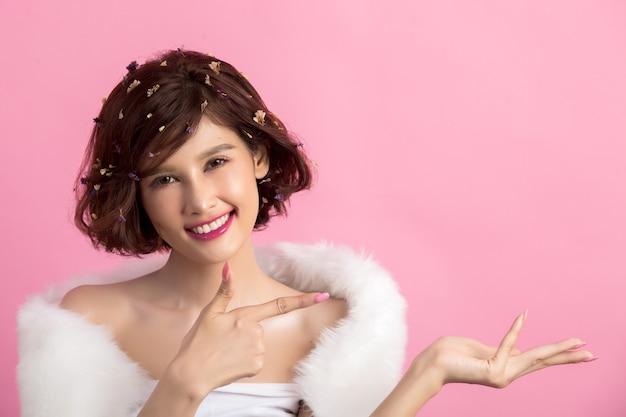 Mooie aziatische die vrouw op roze wordt geïsoleerd Gratis Foto