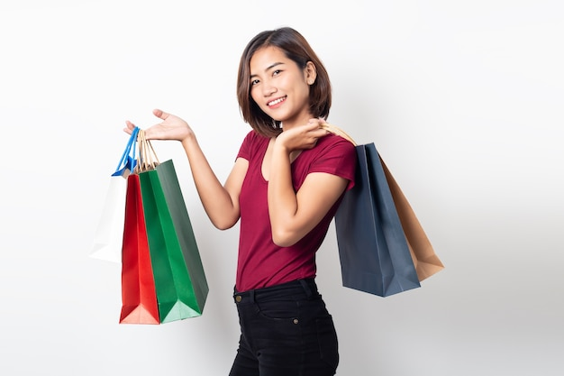 Mooie aziatische jonge vrouw glimlachend bedrijf boodschappentassen geïsoleerd Premium Foto